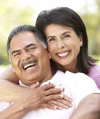 Smiling couple with dental implants in Ocala