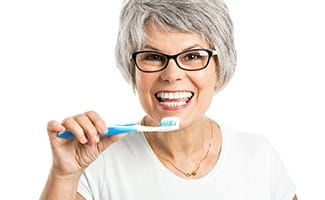 Woman brushing her dental implants in Ocala