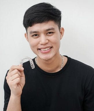 young man holding an Invisalign tray