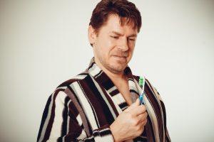 surprised man looking at toothbrush