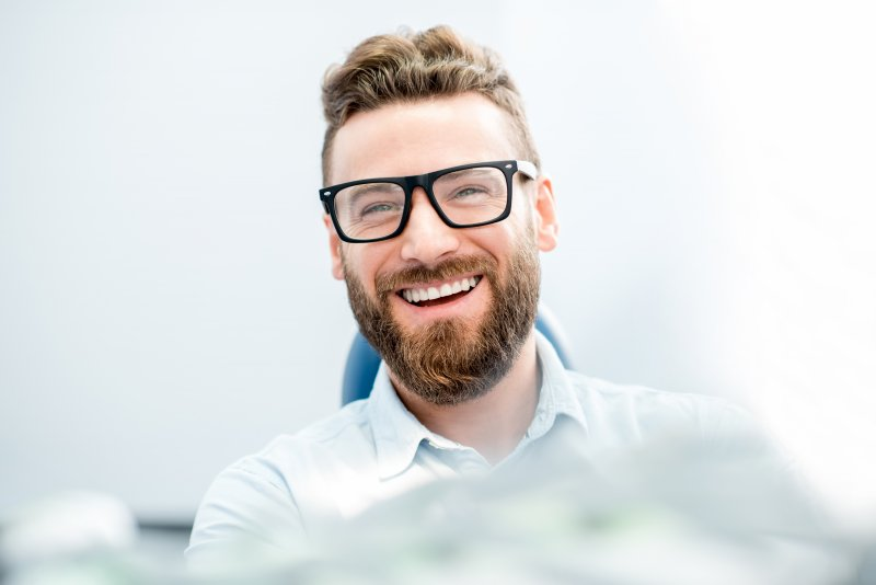 bearded man wearing glasses smiling