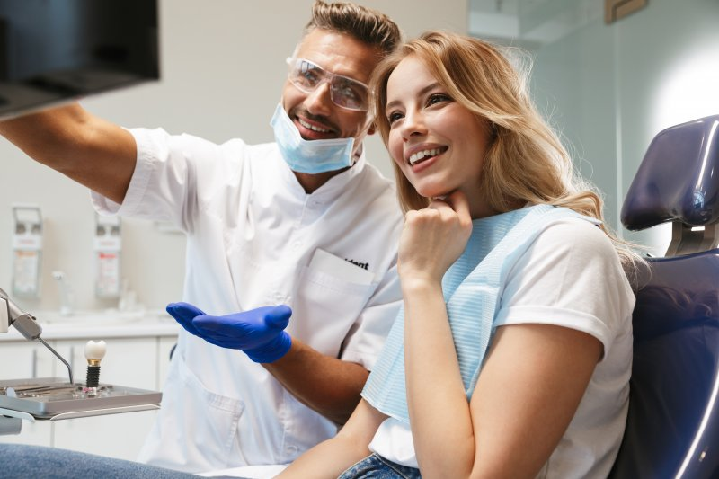 Dentist and patient smiling while looking at X-ray